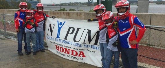 : Young minibikers pose with National Youth Project Using Minibikes banner.